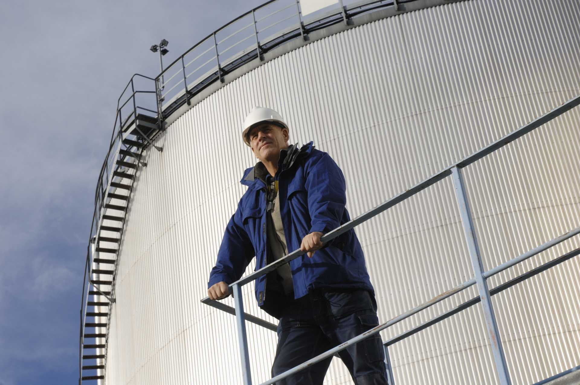 Guy standing on a platform near a storage tank